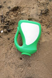 Plastic bottle on beach. Green and white plastic bottle on the beach, with a crab burrow near the mouth Royalty Free Stock Images