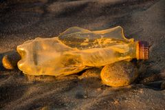 Decaying plastic bottle on beach takes on golden glow of sunset. Beautiful pollution; a plastic bottle decaying on the beach catches the light of the setting sun royalty free stock photography