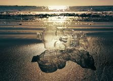 Plastic bottle on the beach. Plastic pollution is killing our marine creatures. The plastic bottle represents death in this picture royalty free stock photography