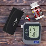 Plastic Bottle with Blood Pressure Support Pills and Digital Blo. Od Pressure Monitor with Cuff on a wooden table. 3d Rendering Stock Photo