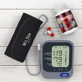 Plastic Bottle with Blood Pressure Support Pills and Digital Blo. Od Pressure Monitor with Cuff on a wooden table. 3d Rendering Royalty Free Stock Photography