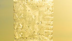 Plastic Bottle Body Parts with Water Drops. A yellowish bottle`s body parts with the water drops inside background photograph Stock Photography
