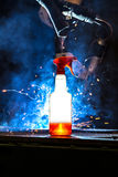 Plastic bottle with cleaning liquid glowing in front CNC Mig wel Royalty Free Stock Photo