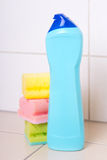 Plastic bottle of cleaning product and three sponges on tiled fl Stock Photos