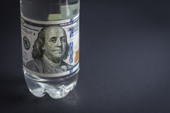 Plastic bottle with a denomination of hundred dollars in place of a label. A dark background Royalty Free Stock Photo