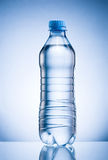 Plastic bottle of drinking water isolated on blue background Stock Photo