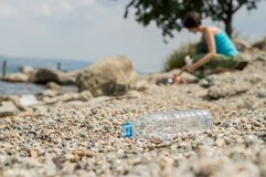 Plastic bottle dumped on the coastal strip with blurry woman picking up the garbage on the background. Royalty Free Stock Photos