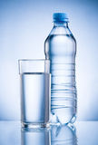 Plastic bottle and glass of drinking water on blue back stock image