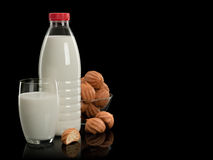 Plastic bottle, glass with milk and a vase with doughnuts Stock Photos