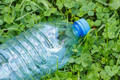 Plastic bottle of mineral water on grass in park, littering of environment Royalty Free Stock Photo