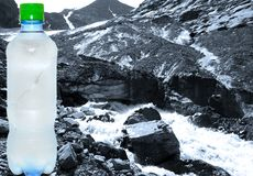 Plastic bottle with pure cold water on a background mountains Stock Image