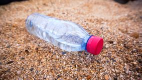 Plastic bottle in the sand. Bottle of fresh water on the sand royalty free stock images