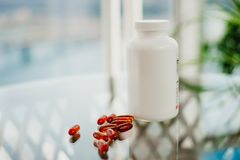 Plastic bottle with scattered brown pills on the glass. stock image