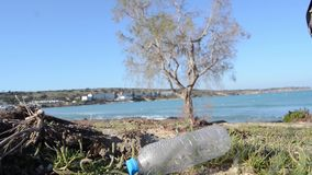 Plastic bottle on the seacost with sea and tree in the backgound, focus change stock footage