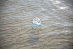 Plastic bottle in shallow sea water, environmental pollution con Royalty Free Stock Photos