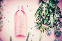 Plastic bottle with tonic or micellar cleansing water with fresh herbs and flowers on pink background, top view. Royalty Free Stock Photography