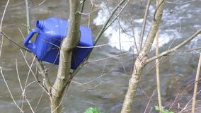Plastic bottle trash branches tree. Plastic bottle trash is thrown in the branches of a tree near a river stock footage