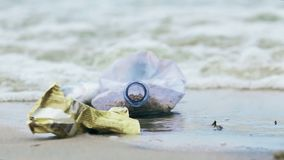 Plastic bottle and trash from tourist ship washed by contaminated water on coast. Stock footage stock video