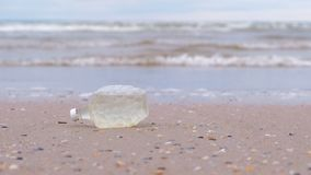 Plastic bottle was brought to the shore on the sandy shore. Environmental pollution by plastic and garbage stock video footage