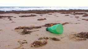 Part of green plastic bottle was brought to the shore on the sandy shore. Plastic bottle was brought to the shore on the sandy shore stock footage