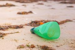 Part of plastic bottle was brought to the shore on the sandy shore. Plastic bottle was brought to the shore on the sandy shore royalty free stock photo