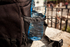 Plastic bottle of water in black backpack Royalty Free Stock Images
