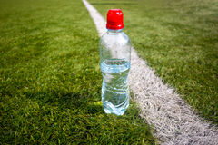 Plastic bottle of water on green grass at football field Royalty Free Stock Images
