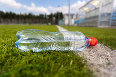 Plastic bottle of water lying on grass soccer field Stock Photo