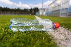 Plastic bottle of water lying on grass soccer field Stock Photo