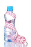 Plastic bottle with water and measuring tape Royalty Free Stock Photos