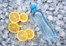 Plastic bottle of water with slice of lemon in ice. Full plastic bottle of water with slice of lemon in ice. top view royalty free stock photo