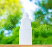 Plastic bottle white on the wood and tree blurry bokeh background in garden. Using wallpaper for package work photo Royalty Free Stock Image