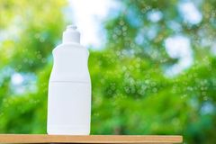 Plastic bottle white on the wood and tree blurry bokeh background in garden. Using wallpaper for package work photo Royalty Free Stock Images