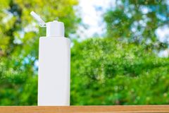 Plastic bottle white on the wood and tree blurry bokeh background in garden. Using wallpaper for package work photo Royalty Free Stock Photo