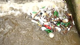 Plastic bottles and another mess turning on water level. Turning of dirty water above weir on small river with muddy water. Stony wall of weir stock footage