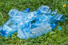 Plastic bottles and bottle caps on grass in park, littering of environment Royalty Free Stock Photography