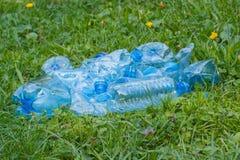 Plastic bottles and bottle caps on grass in park, littering of environment Stock Images