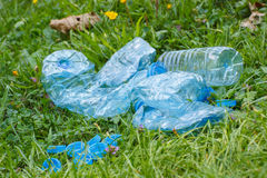 Plastic bottles and bottle caps on grass in park, littering of environment Royalty Free Stock Image