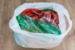 Used colorful plastic bottles on wood background. Ecological disposal of household garbage. Waste sorting. Crumpled PET wrappers in a carrier bag. Compressed royalty free stock photography