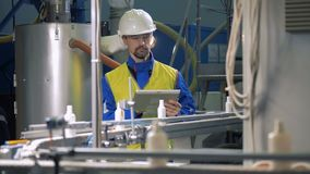 Plastic bottles are falling from the conveyor under control of a male employee stock footage