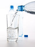 Plastic bottles and glass of water Royalty Free Stock Photography