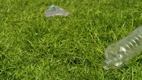Plastic bottles on the grass. Pan shot of plastic garbage. Plastic bottles lie on the grass. Garbage and nature. Problem of plastic pollution of the nature stock footage