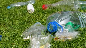 Plastic bottles lie on the grass. Closeup of plastic garbage. Plastic bottles lie on the grass. Garbage and nature. Problem of plastic pollution of the nature stock video footage