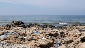Plastic bottles lying on the rocky polluted beach. Environmental problems concept. Plastic bottles lying on the rocky polluted beach. Environmental problems stock video footage