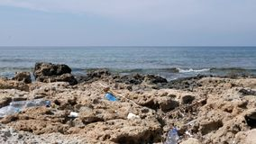 Plastic bottles lying on the rocky polluted beach. Environmental problems concept. Slow motion.  stock footage