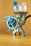 Plastic bottles in a mincer. Stylized idea of recycling plastic bottles with grinder Royalty Free Stock Photo