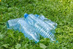Plastic bottles of mineral water on grass in park, littering of environment Royalty Free Stock Images