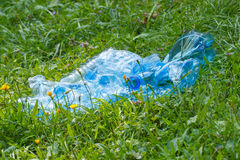 Plastic bottles of mineral water on grass in park, littering of environment Stock Photo