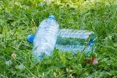 Plastic bottles of mineral water on grass in park, littering of environment Royalty Free Stock Image