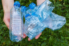 Plastic bottles of mineral water in hand of woman, littering of environment Stock Photo